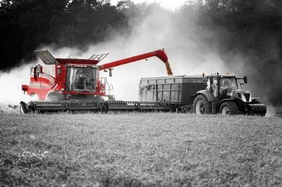 Czerwony kombajn i traktor w żniwa